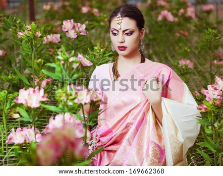beautiful indian girl in the indian national dress on greenhouse - stock photo