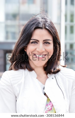 Beautiful Indian girl smiling on a bright summer day looking straight to camera. - stock photo