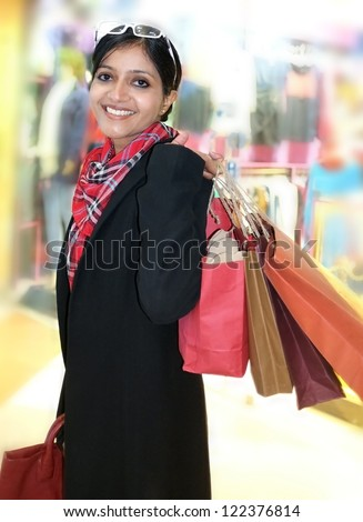 Beautiful Indian shopping woman, happy holding colorful shopping bags in hand. - stock photo