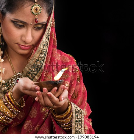 Beautiful Indian woman hands holding diya oil lamp, celebrating diwali festive of lights, traditional sari prayer isolated on black background with copy space on side. - stock photo