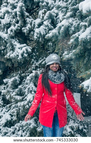 Beautiful Indian woman in a red coat in winter
