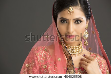 Beautiful Indian woman in glamorous outfit and jewelry with makeup in dark background.