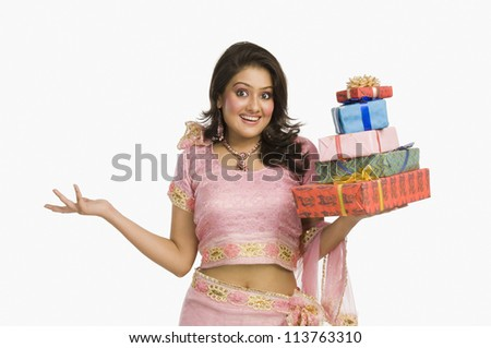 Beautiful Indian woman in traditional dress holding gifts and smiling - stock photo
