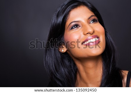 beautiful indian woman looking up on black background - stock photo