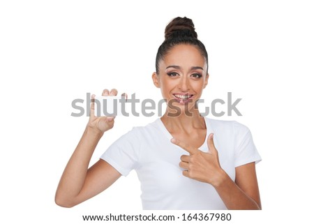 Beautiful Indian woman showing blank empty card. Pointing with finger while standing isolated on white background  - stock photo