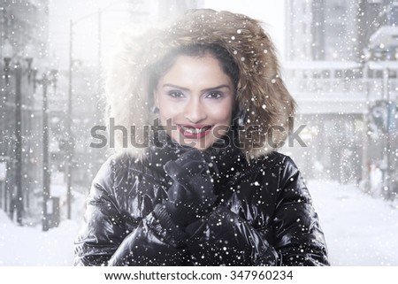 Beautiful indian woman smiling at the camera while wearing winter coat in the city - stock photo