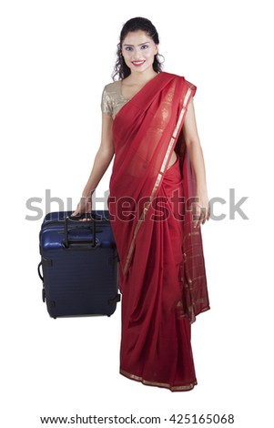 Beautiful Indian woman wearing saree clothes and carrying a suitcase while walking in the studio, isolated on white background - stock photo