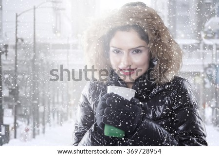 Beautiful indian woman wearing winter coat and enjoy coffee, shot outdoors in snowy day - stock photo