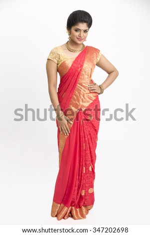 Beautiful Indian young girl standing in traditional Indian saree on white background.  - stock photo