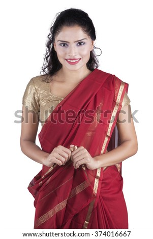Beautiful indian young woman standing in the studio while wearing traditional dress, isolated on white background