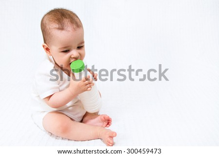 Beautiful infant child baby with bottle on a white background