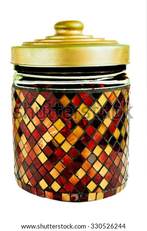 Beautiful inlaid glass jar for foodstuffs with a brass lid insulation against white background. - stock photo