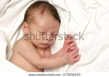 Beautiful innocent newborn sleeping. Adorable little boy relaxing in white sheets after a bath. Infant having sweet dreams - stock photo