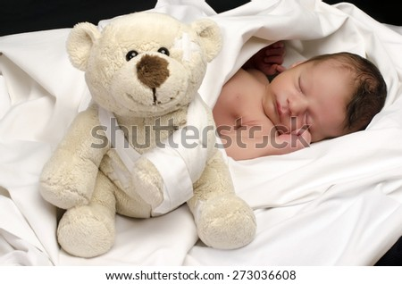Beautiful innocent newborn sleeping. Adorable little boy relaxing in white sheets after a bath and holding close to him his bear toy. Teddy bear protecting the little baby - stock photo