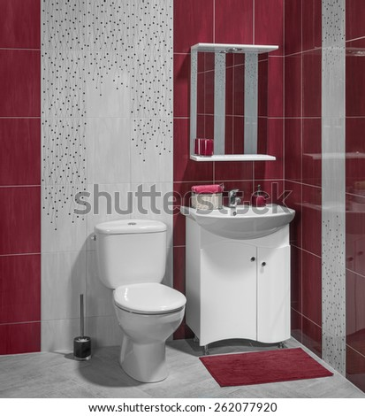 Beautiful interior of bathroom with sink and toilet; decorated with red tiles