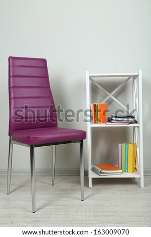 Beautiful interior with modern  color chair,  books on wooden stand, on wall background - stock photo