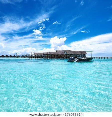 Beautiful island beach with motor boat at Maldives - stock photo