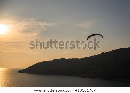 Beautiful island landscape paraglider flying over sea at the sunset time of Phuket, Thailand