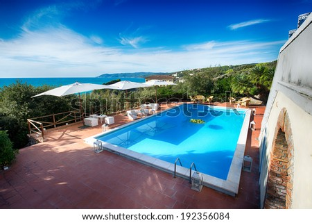 Beautiful italian villa with pool and deckchairs in front of the sea - stock photo