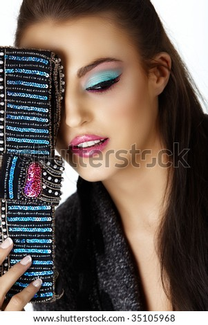 Beautiful Italian woman with bright cat eye style make-up and sequin bag. From 16bit RAW. - stock photo