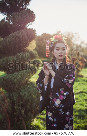 Beautiful Japanese Chinese woman in kimono national posing in the park garden, spring summer, Asia . gracefully folded her hands - stock photo