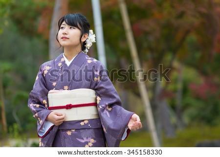 Beautiful Japanese girl in a purple seasonal kimono in a traditional Japanese garden during autumn - stock photo