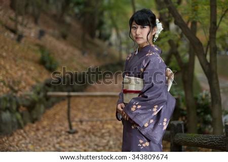 Beautiful Japanese girl in a seasonal kimono in a traditional Japanese garden during autumn