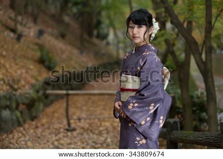 Beautiful Japanese girl in a seasonal kimono in a traditional Japanese garden during autumn - stock photo