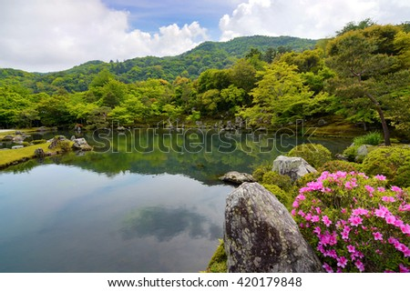 Beautiful Japanese pond garden surrounded by pink azalea flowers and green trees - stock photo