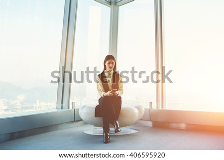 Beautiful Japanese woman student is searching information on web page via cell phone, while is sitting in luxury interior with futuristic design against window with copy space for your advertising
