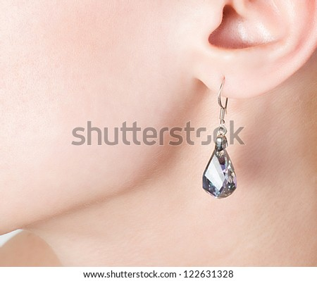 Beautiful  jewellery ear-ring in an ear of young woman - stock photo