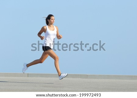 Beautiful jogger woman running fast on the asphalt with the sky in the background
