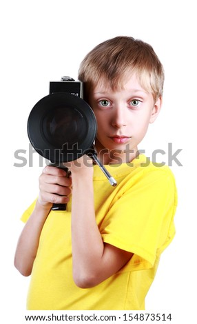 Beautiful joyful blond boy in a yellow t-shirt holds a vintage motion picture camera pointing it to the camera - stock photo