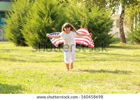 Beautiful joyful girl in a white dress holding a large American flag in a sunny summer day in the park