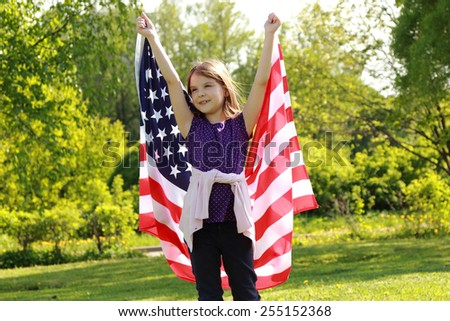 Beautiful joyful girl in a white dress holding a large American flag in a sunny summer day in the park - stock photo