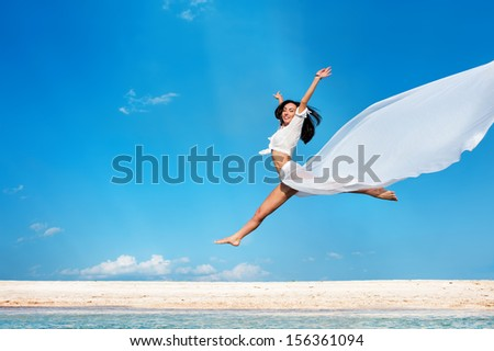 Beautiful joyful girl with white tissue jumping against blue sky - stock photo