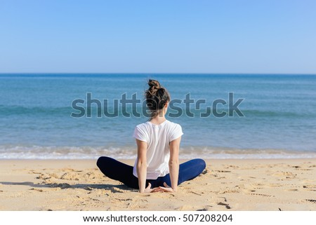 Beautiful joyful woman doing fitness yoga position on the exotic beach outdoor natural background. Back side view