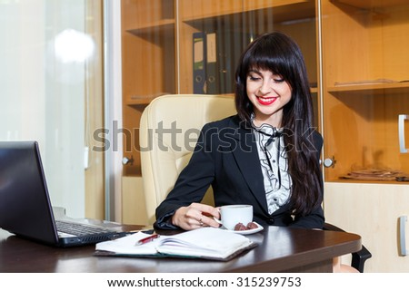 Beautiful joyful woman in office drinking coffee