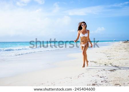 Beautiful joyful woman in white bikini enjoying tropical beach and caribbean summer vacation. Tanned brunette running and enjoying freedom by the sea at Playa Paraiso, Riviera Maya, Mexico. - stock photo