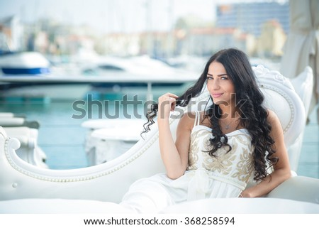 Beautiful joyful woman wearing beautiful elegant dress, enjoying relaxed sunny day out at marina, with boats as background. Beautiful sunset at the yacht club - stock photo