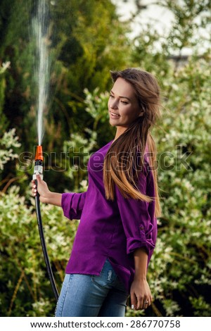 Beautiful joyful young girl in violet shirt poses in a summer garden with a water hose.