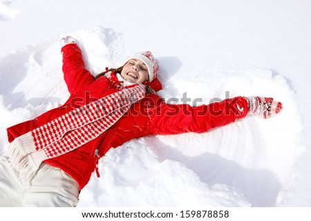 Beautiful joyful young woman laying down on a frozen snow lake moving her arms up and down creating an angel figure shape, playing games while on vacation during a sunny winter day. - stock photo