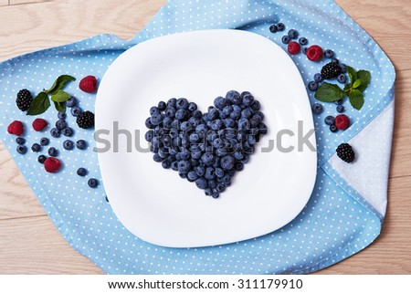 Beautiful juicy ripe natural organic raspberries blackberries blueberries and mint blue tablecloth dots white dish heart shape healthy eating diet sweet delicious vitamins breakfast lunch dinner love - stock photo