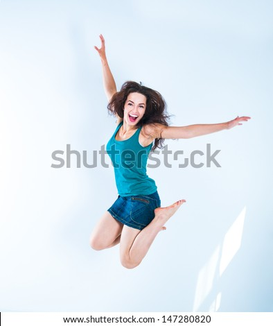 Beautiful jumping girl in a bright room