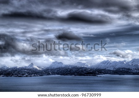Beautiful Kenai mountains in Alaska with the Kachemak bay with storm clouds in winter. - stock photo