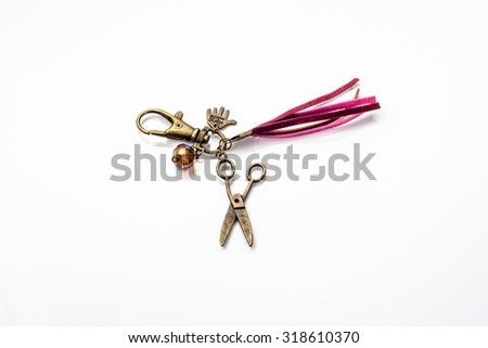 Beautiful keychain jewelry made with antique gold, crystal glass, leather straps and pendant in shape scissors isolated on white background. - stock photo
