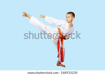 Beautiful kick foot performed by a boy with orange belt - stock photo
