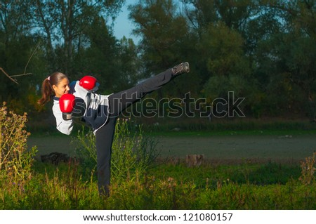 Beautiful kickboxing girl exercising high kick in the nature at night.