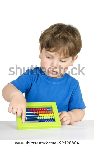 Beautiful kid at the table with an abacus - isolated over a white background. - stock photo