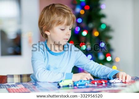Beautiful kid boy playing with cars and toys at home, indoor. funny child having fun with gifts. Colorful christmas lights on background. Family, holiday, kids lifestyle conceplt. - stock photo